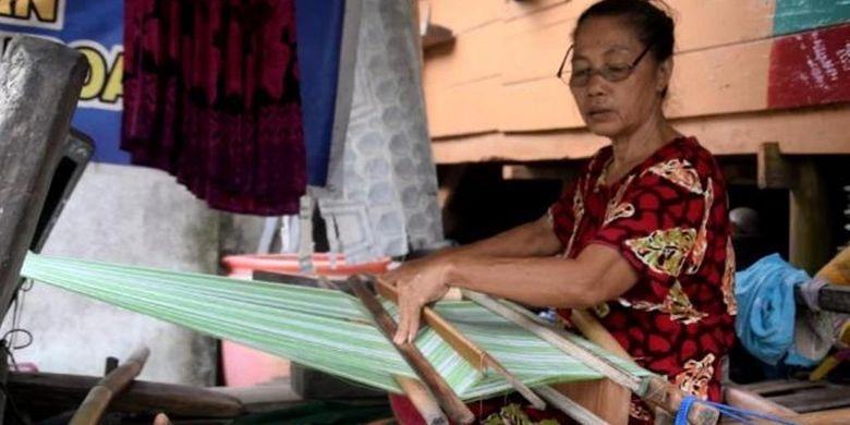 Seorang warga Kampung Tenun Sulaa, Kelurahaan Sulaa, Kecamatan Betoambari, Kota Baubau, Sulawesi Tenggara, Kamis (14/3/2019) sedang menenun di depan rumahnya.