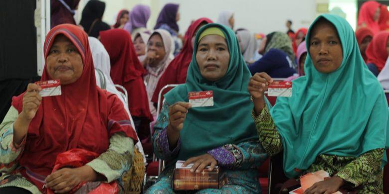 Ibu-ibu Keluarga Penerima Manfaat menunjukkan Kartu Keluarga Sejahtera (KKS) saat acara penyaluran  Bantuan Pangan Non Tunai (BPNT) kepada Keluarga Penerima Manfaat (KPM) di Asramah Haji Donohudan, Kabupaten Boyolali, Jumat (1/2/2019).