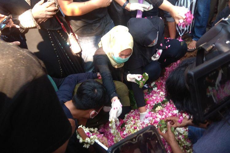 Istri dan Anak Didi Kempot menabur bunga di pusara sang maestro yag dimakamkan di Tempat Pemakaman Umum (TPU) Desa Majasem, Kecamatan Kendal, Kabupaten Ngawi, Jawa Timur, pada Selasa (5/5/2020) petang.