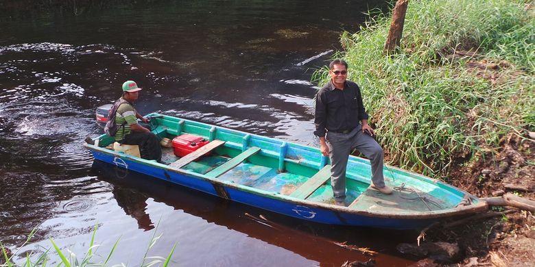 Mahyudin berdiri di atas salah satu perahu yang ia sewakan kepada Riau Andalan Pulp and Papper. Tak lagi mencuri kayu, kini ia mendapat kesempatan kerja sama dengan RAPP juga bantuan pinjaman modal usaha.