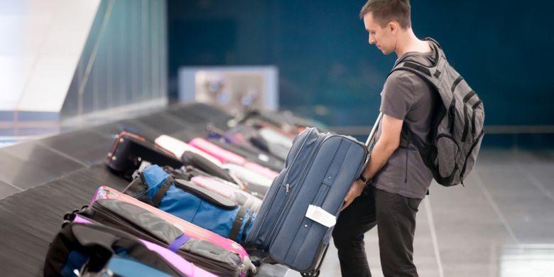 ILUSTRASI - Penumpang mengambil koper di bandara.