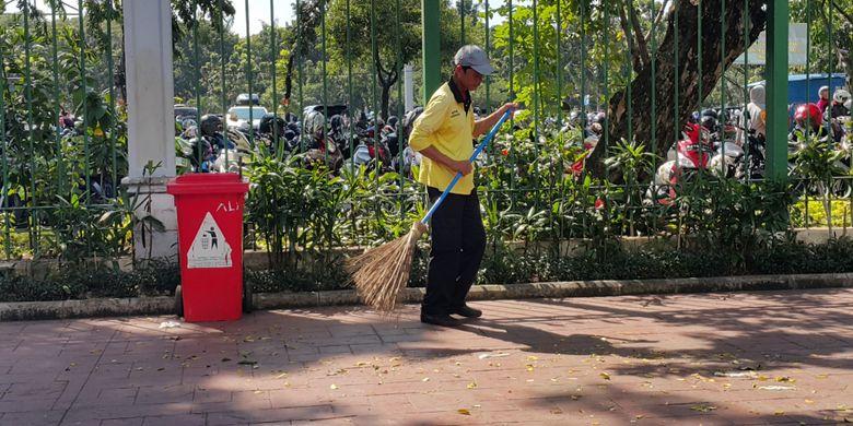 Ali Santoso (48) membersihkan sampah-sampah yang mengotori pedestrian di luar kawasan Monumen Nasional (Monas) di Jalan Medan Merdeka Selatan, Jakarta Pusat, Rabu (28/6/2017). Ia tidak libur pada hari Lebaran 2017.