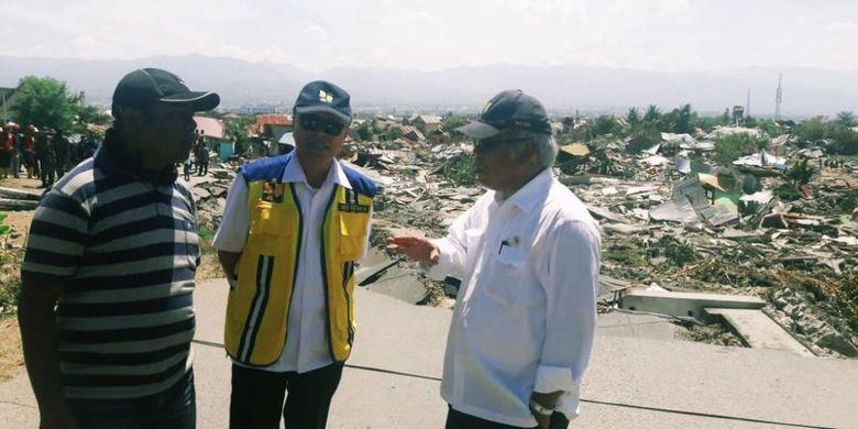 Menteri Pekerjaan Umum dan Perumahan Rakyat (PUPR) Basuki Hadimuljono didampingi Ketua Tim Satgas Penanganan Bencana Sulawesi Tengah Kementerian PUPR Aries S Moerwanto tengah berbincang dengan warga Petobo, Palu, Jumat (5/10/2018).