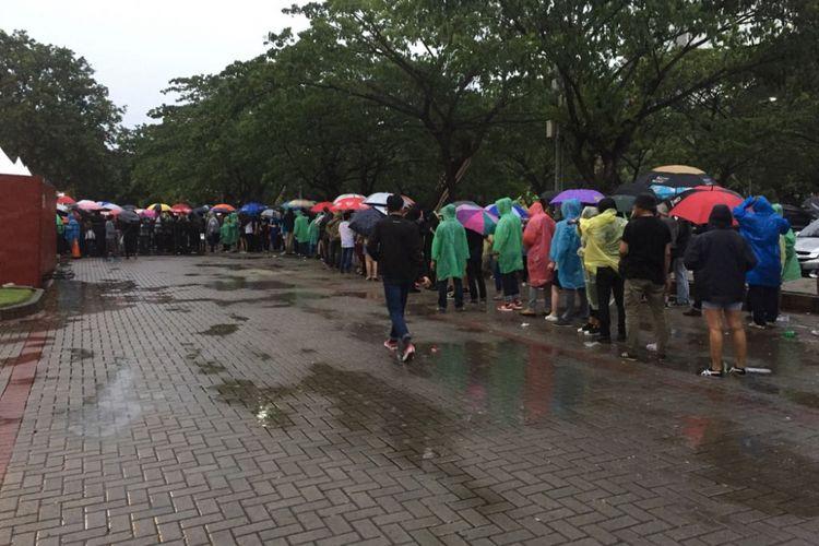 Di bawah guyuran hujan para penonton dengan sabar mengantre masuk Econvention Ancol, Jakarta Utara, Minggu (14/1/2018) untuk menyaksikan konser musisi asal Inggris Liam Gallagher.