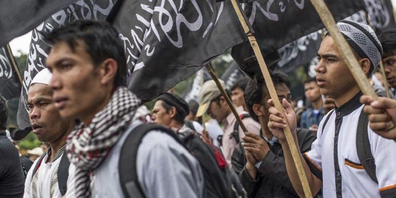 Massa dari Hizbut Tahrir Indonesia membawa bendera saat demo di Jakarta pada 18 Juli 2017. Mereka menentang rencana pemerintah yang akan membubarkan HTI.