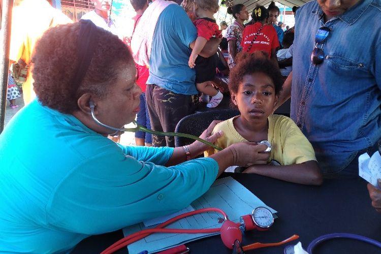 Salah satu anak di Kampung Puay, Distrik Sentani Timur, Kabupaten Jayapura, Papua, sedang diperiksa dokter saat pengobatan massal yang diselenggarakan oleh Ikatan Masyarakat Papua Alumni Jawa Timur bekerjasama dengan Yayasan Dos Ni Roha (DNR) Jakarta, Selasa (9/4/2019)
