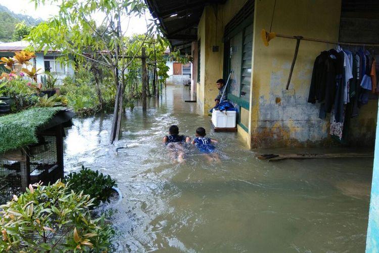 Dua orang anak di Tambelan terlihat asik berenang di halaman rumahnya yang kebanjiran, Minggu (14/1/2018). Kawasan Tambelan dilanda Banjir dan tanah Longsor pada akhir pekan ini.