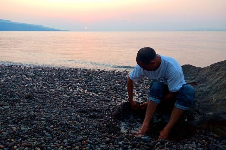 Wisatawan sedang merasakan air panas alami, di bibir pantai Kawaliwu di Kelurahan Riangkotek, Kecamatan Lewo Lema, Flores Timur, Nusa Tenggara Timur, Kamis (11/10/2018).
