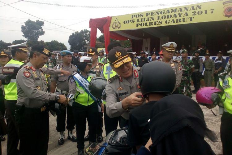 Asops Polri Irjen Pol Iriawan membagikan helm gratis kepada pengguna sepeda motor yang tidak menggunakan helm saat melakukan peninjauan kesiapan operasi lilin di Pos Pengamanan Limbangan Polres Garut, Jumat (22/12/2017) sore.