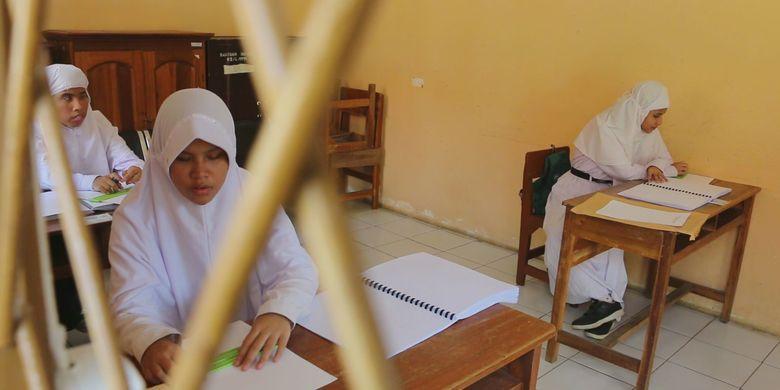 Tiga orang pelajar mengerjakan UN SMP di SLB A Beringin Bhakti, Kecamatan Talun, Kabupaten Cirebon, Jawa Barat, Senin (22/4/2019). Mereka menilai soal Bahasa Indonesia banyak yang panjang sehingga menyulitkan dengan tenggah waktu 120 menit.