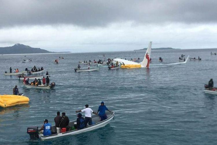 Penduduk setempat mendekati pesawat dengan menggunakan perahu kecil untuk menyelamatkan penumpang dari pesawat <a href='http://medan.tribunnews.com/tag/air-niugini' title='Air Niugini'>Air Niugini</a> yang jatuh di pulau terpencil Weno, di <a href='http://medan.tribunnews.com/tag/mikronesia' title='Mikronesia'>Mikronesia</a>, Jumat (28/9/2018). (AFP/James Yaingeluo)