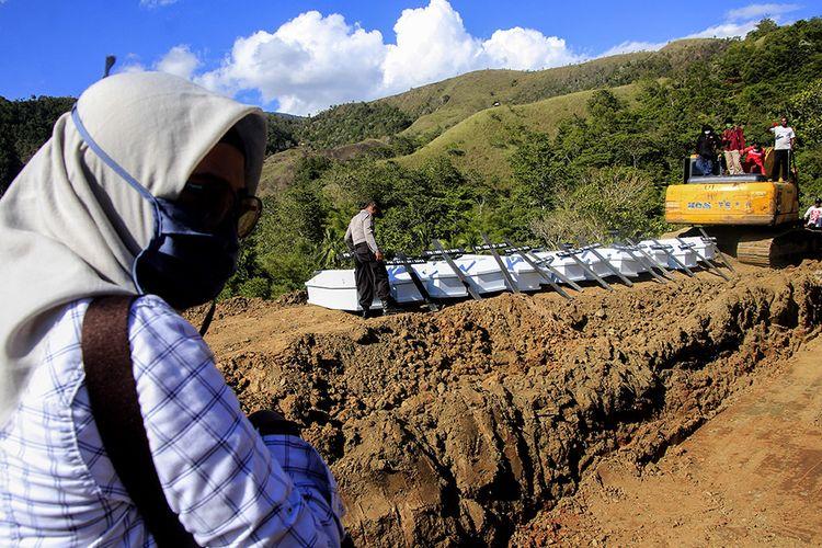 Personel kepolisian bersiap memasukkan peti berisi jenazah korban banjir bandang Sentani yang dikuburkan secara massal di Pemakaman Umum Kampung Harapan Sentani, Jayapura, Papua, Rabu (27/3/2019). Sebanyak 20 jenazah yang belum teridentifikasi dikuburkan secara massal.