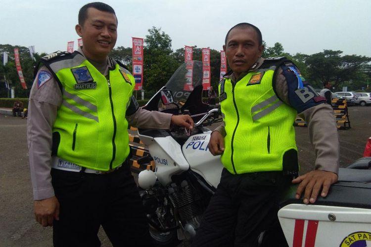 Aipda Martulis bersama rekannya dari Polda Metro Jaya berpose sebelum mengawal rombongan mudik gratis Alfamidi dari area parkir Museum Purna Bakti Pertiwi Taman Mini Indonesia Indah (TMII) pada Selasa, 12 Juni 2018.