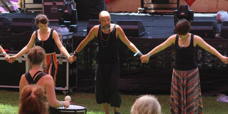 Para peserta Bali Spirit Festival sedang bergandengan tangan saat mengikuti salah satu rangkaian kegiatan di event tersebut.
