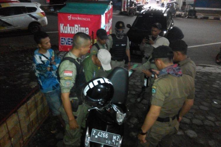 Petugas Satpol PP Kota Tasikmalaya menemukan penjual jamu di pinggir jalan yang menjual miras di kok motor, Sabtu (1/12/2018).