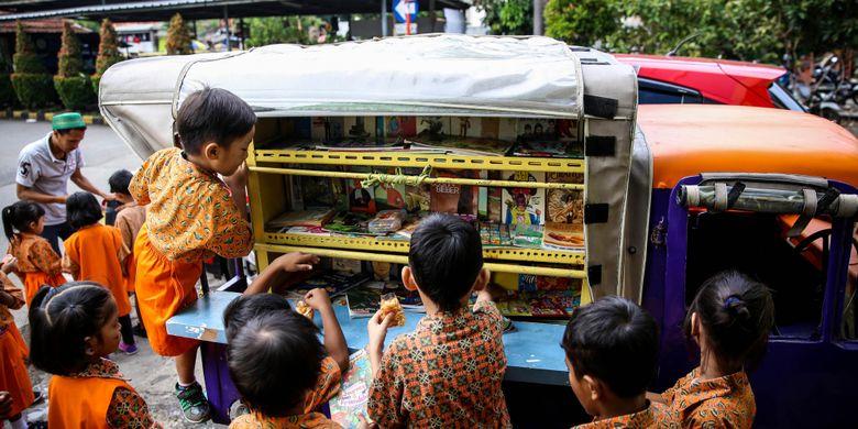 Anak-anak sekolah Paud saat membaca buku di bemo perpustakaan saat jam istirahat di Rusun Karet Tengsin, Jakarta, Jumat (7/12/2018). Pak Sutino (58) adalah sopir bemo yang merintis bemo tuanya menjadi perpustakaan keliling bagi anak-anak sejak tahun 2013.