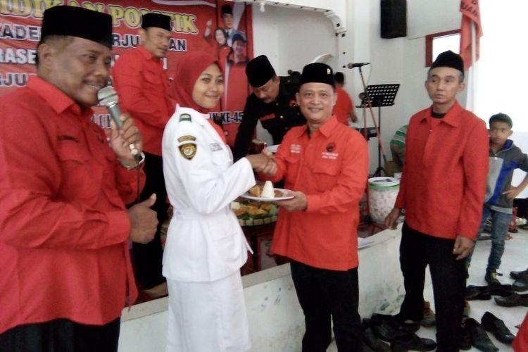 Fahrudin Bisri Slamet,  Ketua DPC PDIP Kabupaten Demak, Jateng, memberikan potongan tumpeng kepada salah satu kader muda partai, pada perayaan ulang tahun ke-45 PDI-P di Kantor DPC PDIP Demak, Minggu (14/1/2018).