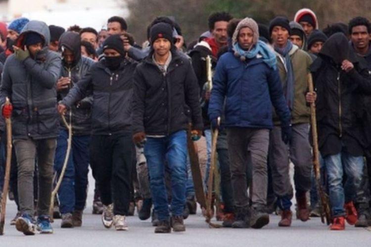 Sekelompok migran menggunakan tongkat selama bentrokan terjadi. (EPA via BBC)