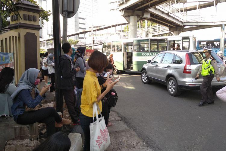Penumpang Transjakarta keluar dari bus karena macet parah di Simpang Matraman, Selasa (10/4/2018)