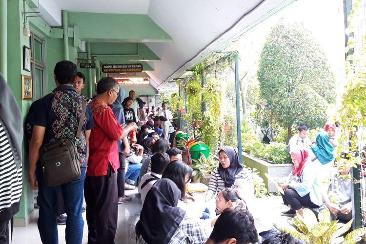 Para orangtua calon murid duduk di lantai SMAN 68, Jakarta Pusat, menunggu pendaftaran PPDB, Senin (24/6/2019)