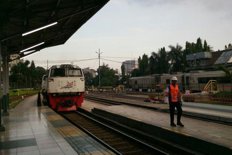Petugas tengah membantu memberikan peringatan masinis kereta agar melaju pelan saat memasuki stasiun Bandung.