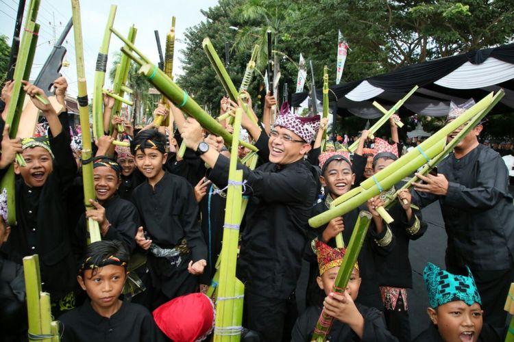 Bupati Banyuwangi Abdullah Azwar Anas angkat senjata bersama anak-anak dalam Festival Memengan Tradisional 2017 yang digelar pada Sabtu (22/7/2017). Pemerintah Banyuwangi menekankan permainan tradisonal merupakan sarana pendidikan karakter anak.