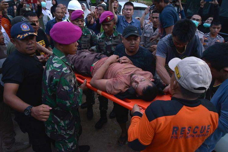 Petugas menggotong salah seorang penambang yang selamat dari lokasi Pertambangan Emas Tanpa Izin (PETI) Desa Bakan, Kecamatan Lolayan, Kabupaten Bolaang Mongondouw, Sulawesi Utara, Rabu (27/2/2019). Sebanyak 23 orang penambang tertimbun longsor, 19  orang di antaranya selamat dan 4 orang tewas.
