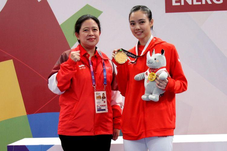 Menko PMK Puan Maharani mengalungkan medali emas ke alet wushu andalan Indonesia Lindswell Kwok dalam gelaran Asian Games 2018, di Jakarta, Senin (20/8/2018).