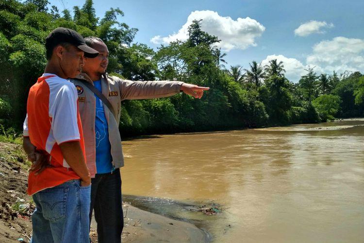 Supriyanto (kaos oranye) berdiri di pinggir sungai Progo, Dusun Jati, Desa Kalinegoro, Kecamatan Mertoyudan, Kabupaten Magelang, mencari Ulum (11) anaknya yang hanyut sejak Rabu (6/12/2017) sore.