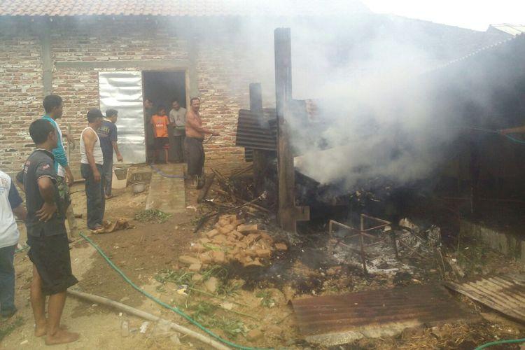 Warga membantu memadamkan api yang membakar gudang kayu milik Murtaji (80), warga Desa Kutukolon, Kecamatan Jetis, Kabupaten Ponorogo, Jawa Timur, Senin (17/7/2017) sore.