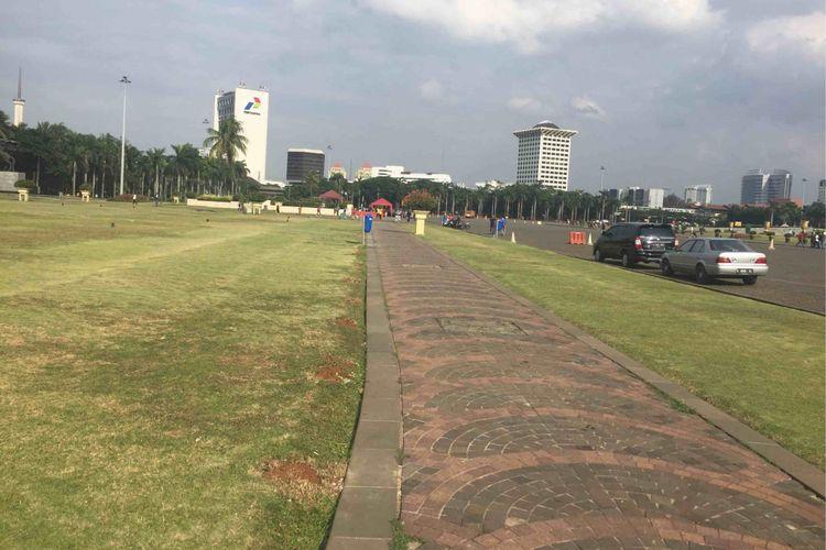 Petugas perawatan taman di Monas menyebut rumput taman di kawasan Monas mulai menguning setelah Pemprov DKI Jakarat memperbolehkan pengunjung menginjak rumput taman, Sabtu (13/1/2018).