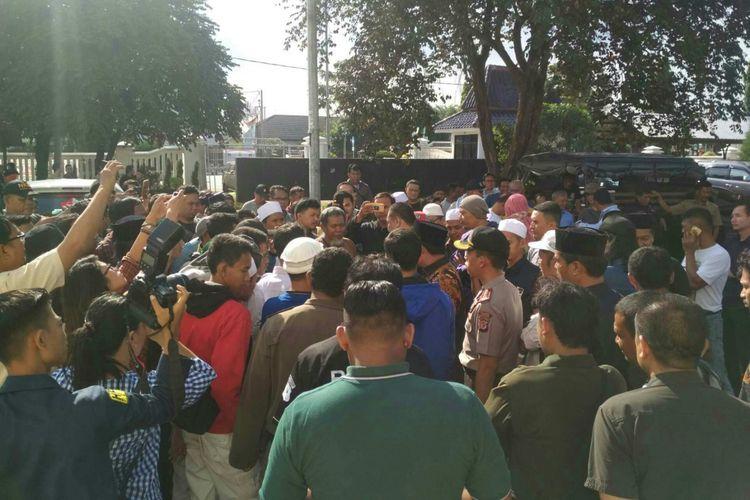 Massa berkumpul di halaman parkir DPRD Kabupaten Karawang. Mereka menuntut Anggota DPRD Karawang Hitler Nababan meminta maaf secara terbuka.