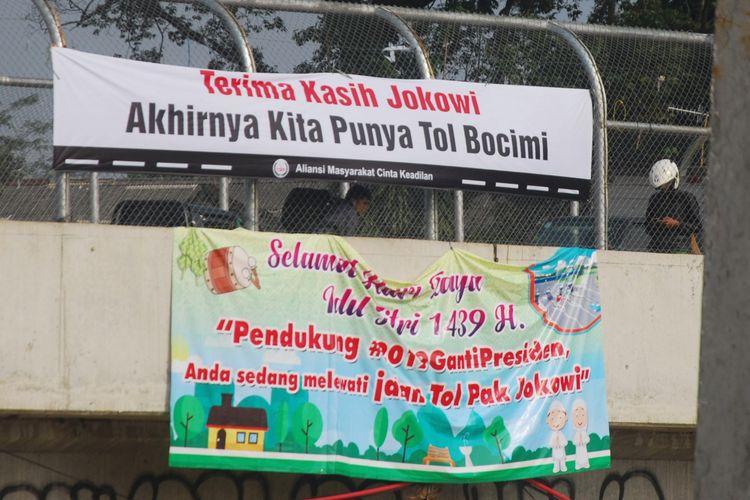 Spanduk bertuliskan Terima Kasih Jokowi, Akhirnya Kita Punya Bocimi dan  Pendukung #2019GantiPresiden, Anda sedang melewati Jalan Tol Pak Jokowi terpasang di tol fungsional Bogor-Ciawi-Sukabumi (Bocimi), Senin (11/6/2018).
