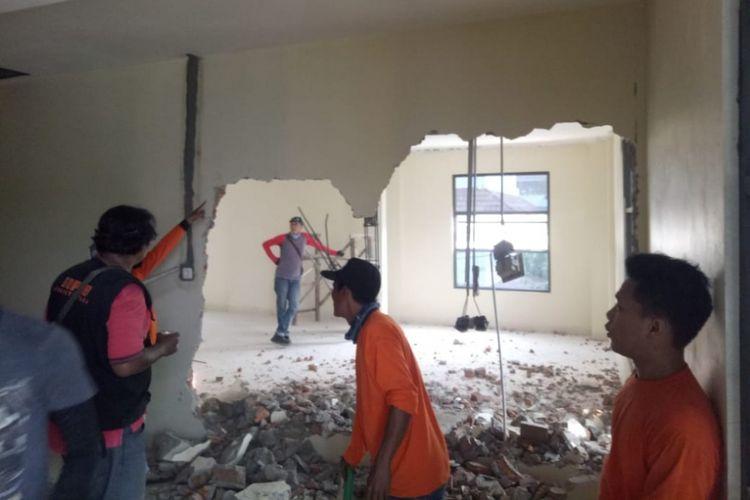 Petugas tengah membongkar sebuah bangunan di Tanjung Priok yang menyalahi IMB, Kamis (12/7/2018).