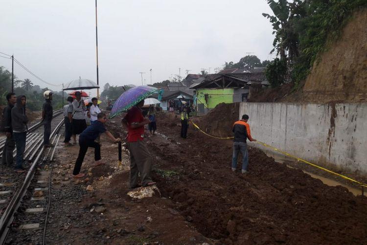 Petugas kepolisian dari Polsek Cicurug memasang garis polisi di tempat kejadian perkara tanah longsor di Cicurug, Sukabumi, Jawa Barat, Kamis (10/1/2019).
