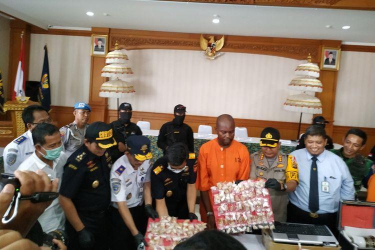 warga negara Tanzania berinisial Abdurahman alias ARA (baju orange)  menunjukkan barang bukti narkoba yang coba diselundupkan ke Bali