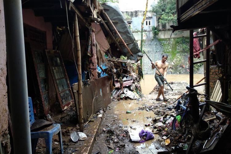 Warga Bidaracina membersihkan sisa-sisa banjir yang melanda wilayahnya Jumat (9/2/2018). Banjir beberapa hari lalu membuat kawasan ini terendam air dan membawa banyak lumpur