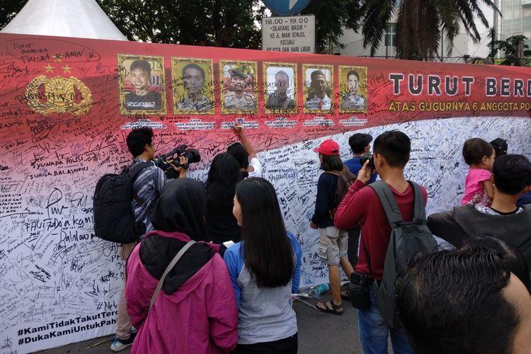 Warga berbondong-bondong ungkapkan bela sungkawa bagi anggota kepilisian yang gugur di Mako Brimob. Mereka menuliskan ungkapan duka di atas sebuah spanduk yang dibenatangan di CFD Minggu (13/5/2018).