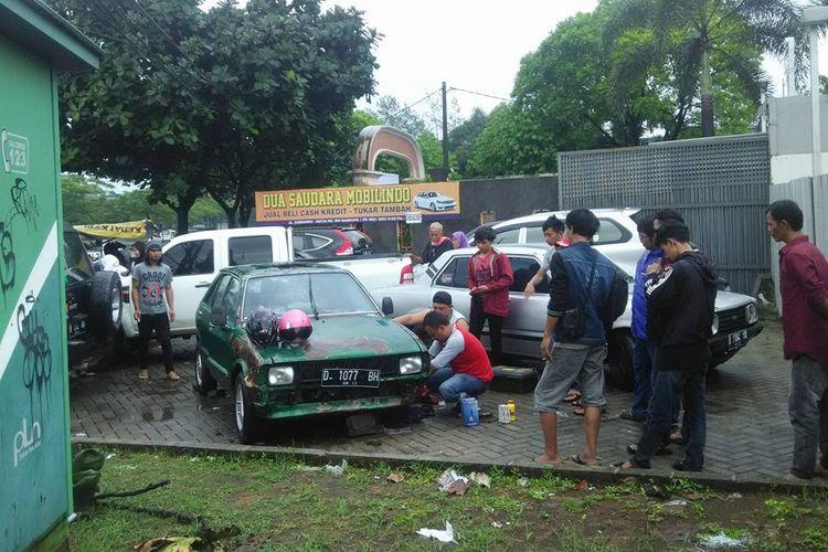 Sejumlah warga sedang memperbaiki mobil Charade yang rusak