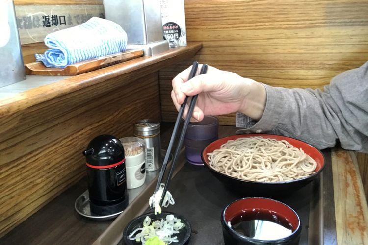 Ambil kondimen dengan sumpit dan tambahkan ke kuah.