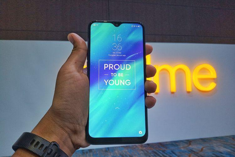 Ilustrasi bagian depan Realme 3 dalam genggaman. Ponsel tersebut memiliki layar sebesar 6,22 inci dengan resolusi 720 x 1.520 piksel. Tampak ada poni tetesan air (dewdrop) yang mewarnai desain muka ponsel tersebut.