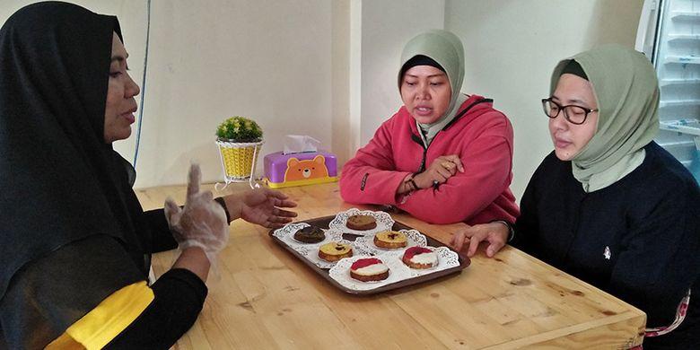 Nikmatus (kiri) saat berbincang dengan para konsumen terkait kue lumpur produksi tokonya di Gresik, Senin (29/10/2018).