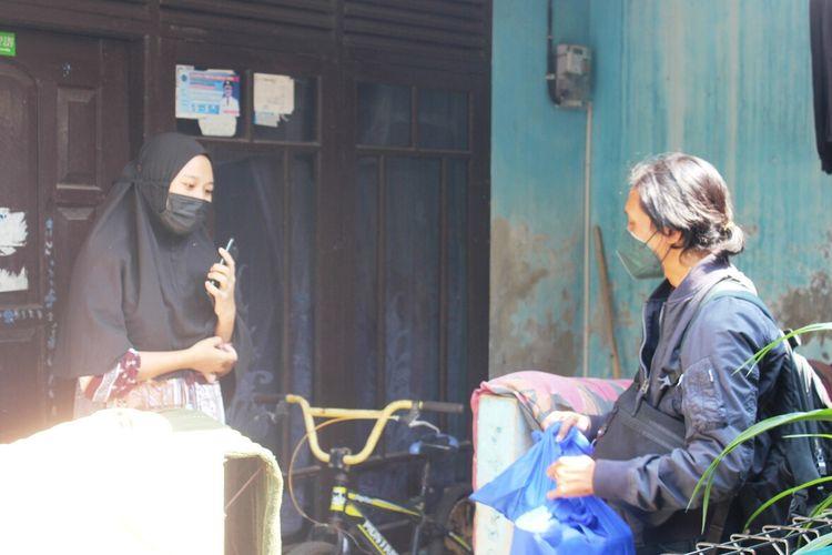 Wisnu Sopian (25) menemui seorang warga yang sedang menjalani isolasi mandiri di rumah untuk memberikan bantuan berupa makanan, vitamin dan suplemen.