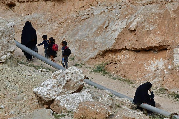Pengungsi perempuan dan anak-anak meninggalkan Desa Baghouz di Suriah Timur, Suriah, basis terakhir ISIS yang dihancurkan Tentara Demokratik Suriah (SDF) dukungan Amerika Serikat. Gambar diambil pada 14 Maret 2019.