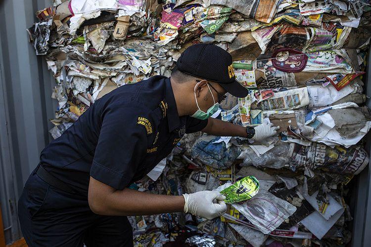 Petugas bea cukai memeriksa kontainer yang dipenuhi sampah asal Australia di sebuah pelabuhan di Surabaya, Selasa (9/7/2019). Indonesia menyatakan akan mengembalikan sampah dalam jumlah besar mencapai 210 ton ke negara asal pengirim, Australia.
