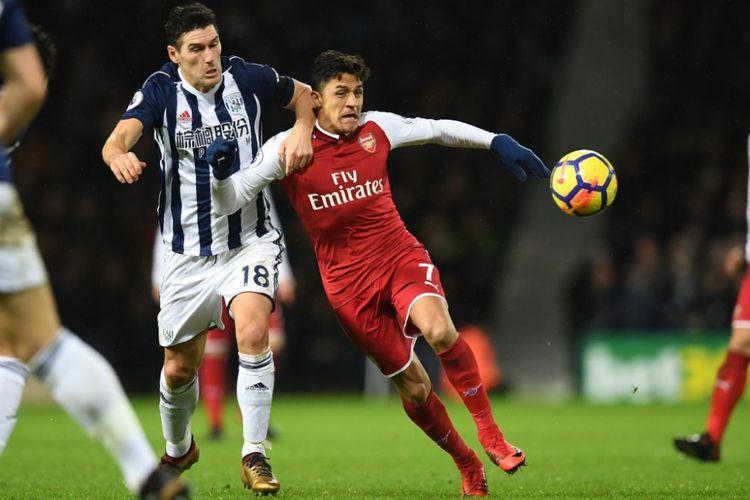 Alexis Sanchez dibayang-bayangi Gareth Barry saat Arsenal bertandang ke markas West Bromwich Albion pada laga pamungkas tahun di The Hawthorns, Minggu (31/12/2017).