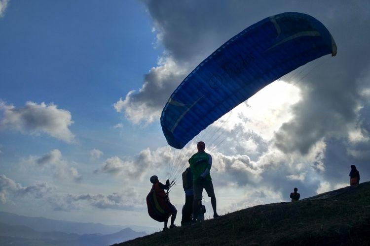 Salah satu peserta festifal paralayang hendak terbang dari puncak Bukit Tunggangan, Kecamatan Durenan Trenggalek, Jawa Timur, Minggu (1/7/2018).