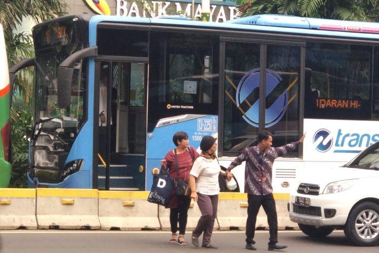 Petugas Transjakarta membantu penumpang menyeberang jalan. Penumpang turun di tengah jalan karena bus transjakarta terjebak macet imbas adanya demo di Gedung Bawaslu RI, Jumat (10/5/2019).
