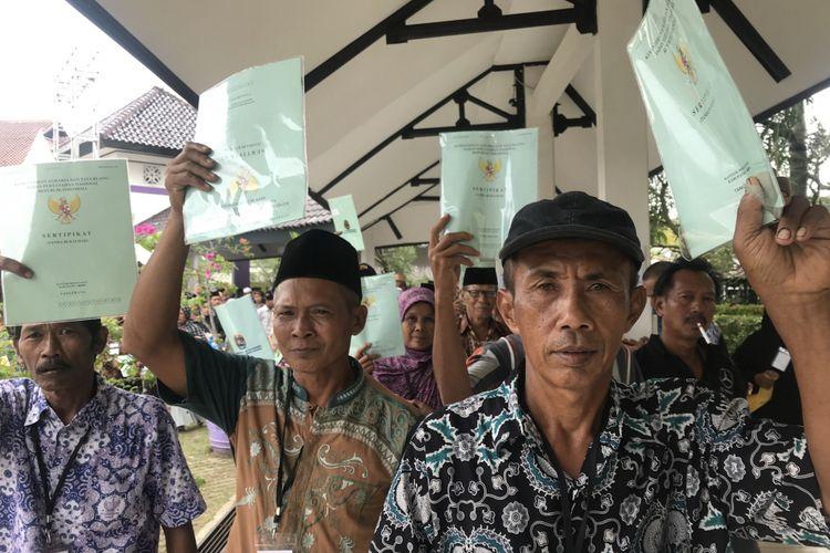 Sejumlah warga Kabupaten Tangerang, Banten, menunjukkan sertifikat tanahnya usai dibagikan oleh Presiden Joko Widodo (Jokowi) di Lapangan Maulana Yudha, Tigaraksa, Kabupaten Tangerang, Senin (18/2/2019)