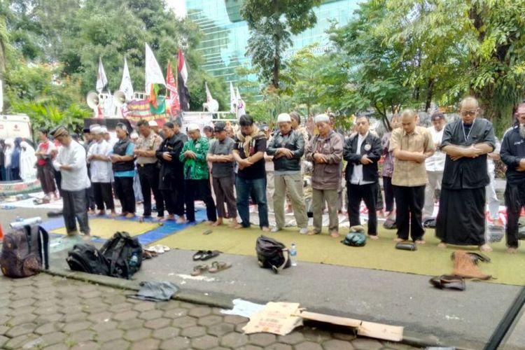 Sejumlah massa pembela Buni Yani menghentikan sementara orasinya untuk melakukan shalat Dzuhur berjamaah didepan Gedung Dinas Perpustakaan dan Kearsipan, Kota Bandung, di jalan Seram, Selasa (14/11/2017).